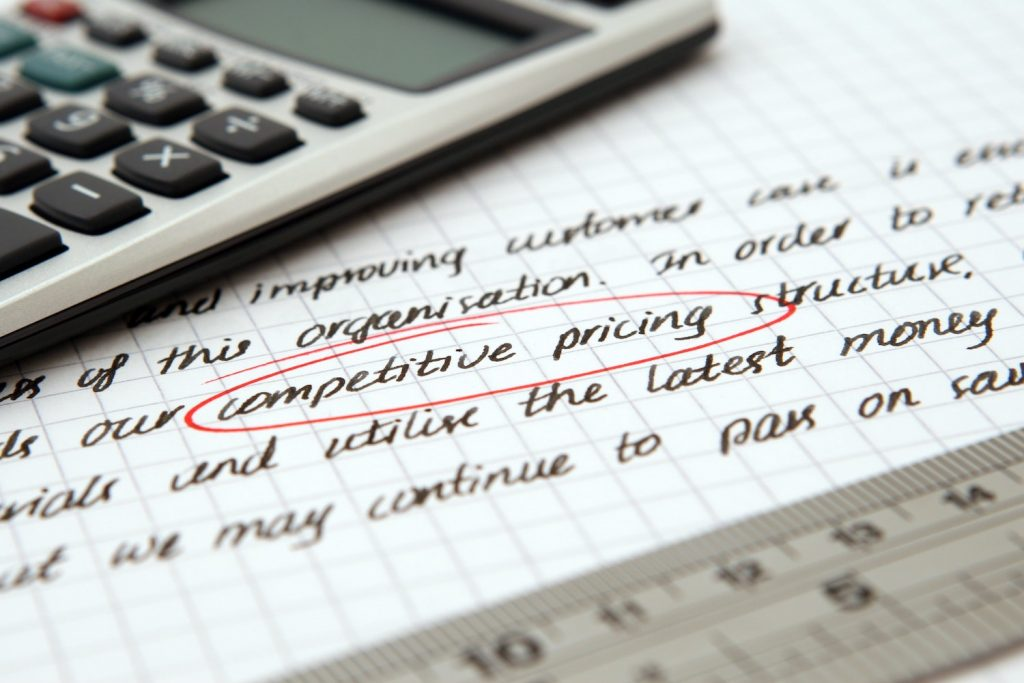 Close up of competitive pricing strategy notes on paper next to a scientific calculator